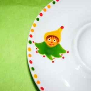 Détail coquetier assiette en porcelaine peinte à la main, décor lutins circus jaune vert rouge
