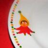 Détail petite assiette ronde en porcelaine peinte à la main, décor lutins circus en vert jaune et rouge