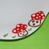 Détail petite assiette plate forme fleur en porcelaine blanche peinte à la main, décors champignons rigolos